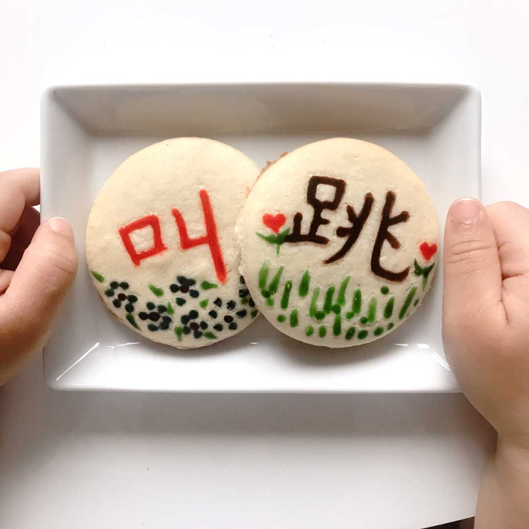 toddler hands holding plate with 2 cookies decorated with Chinese characters