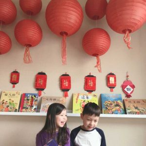 happy children sitting under red paper lanterns and chinese new year decorations