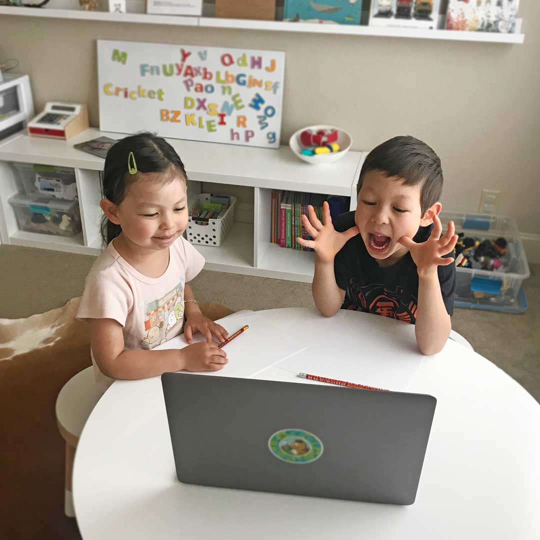 girl and boy in front of laptop