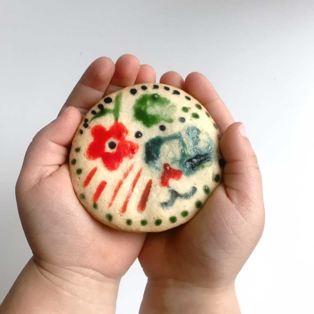 toddler hands holding decorated sugar cookie