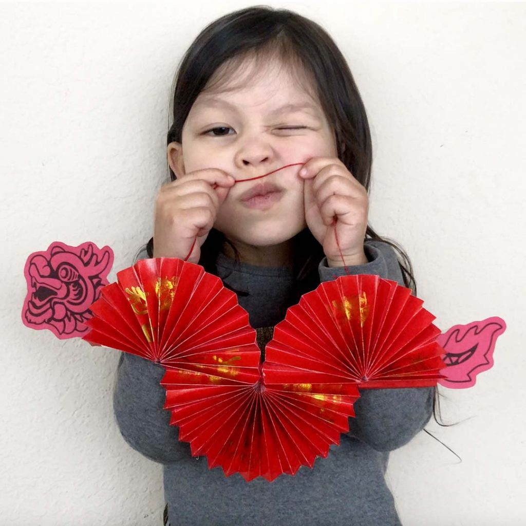 child holding Chinese New Year dragon decoration made out of red envelopes