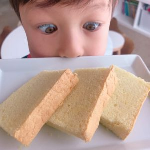 boy looking at slices of taiwanese sponge cake on a plate