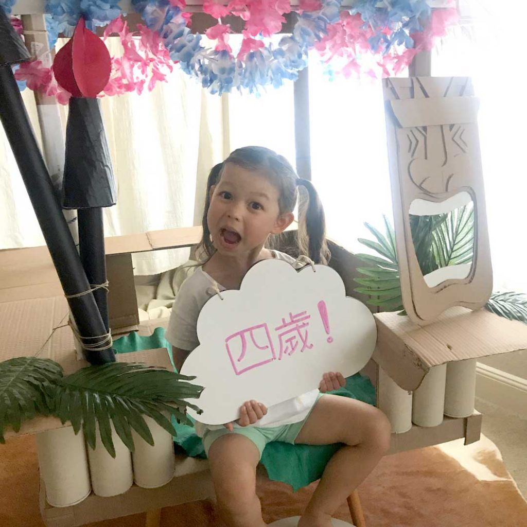 """girl holding a cloud shaped sign that says """"四歲"""""""