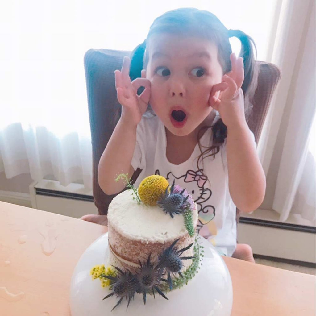 girl with surprised look in front of homemade birthday cake