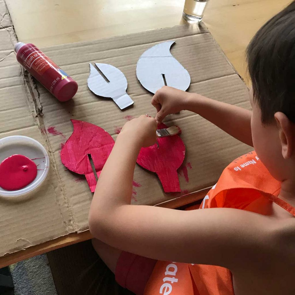 child painting cardboard flames with red paint