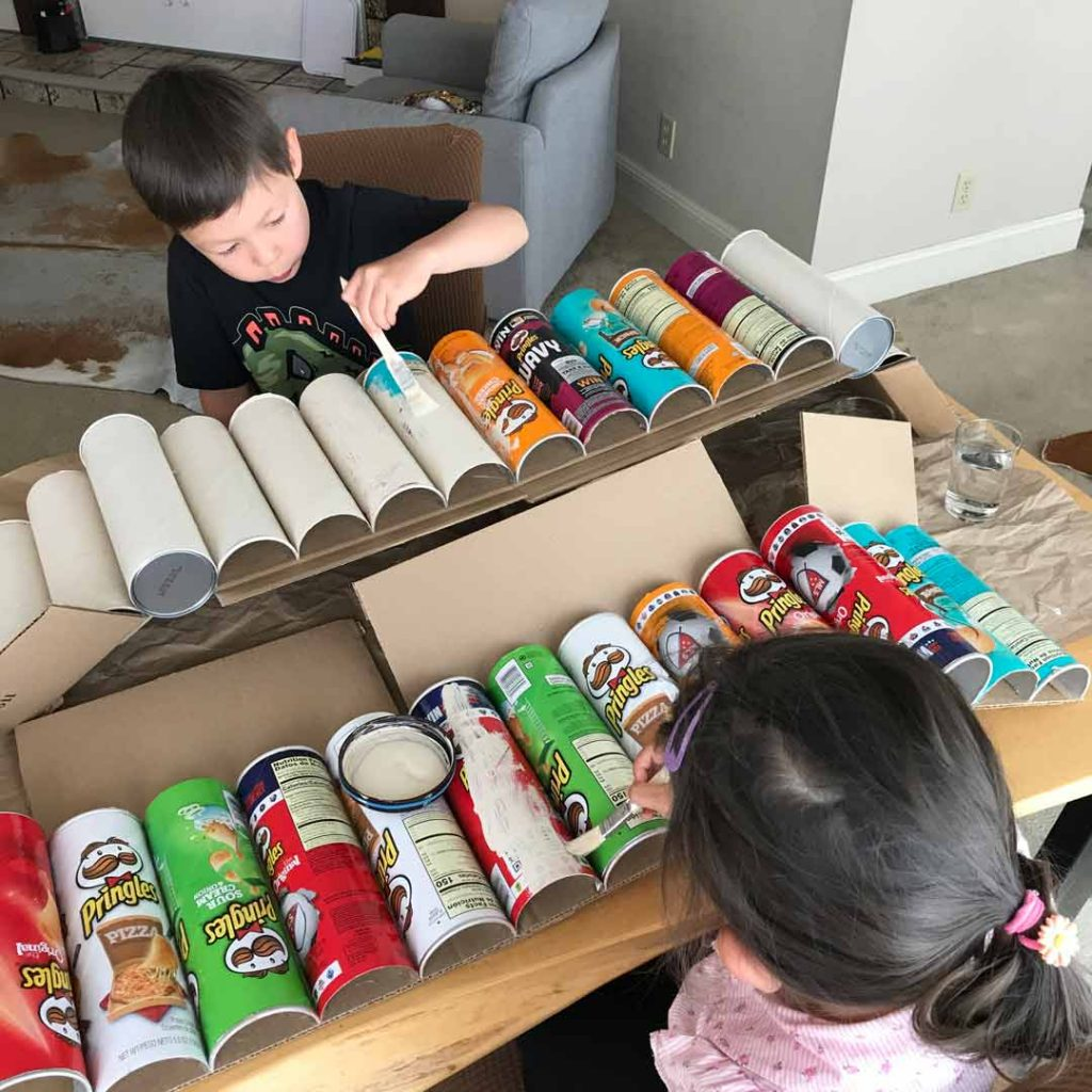 children painting pringles cans for diy project