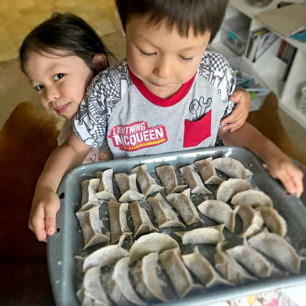 boy holding a tray of uncooked potstickers