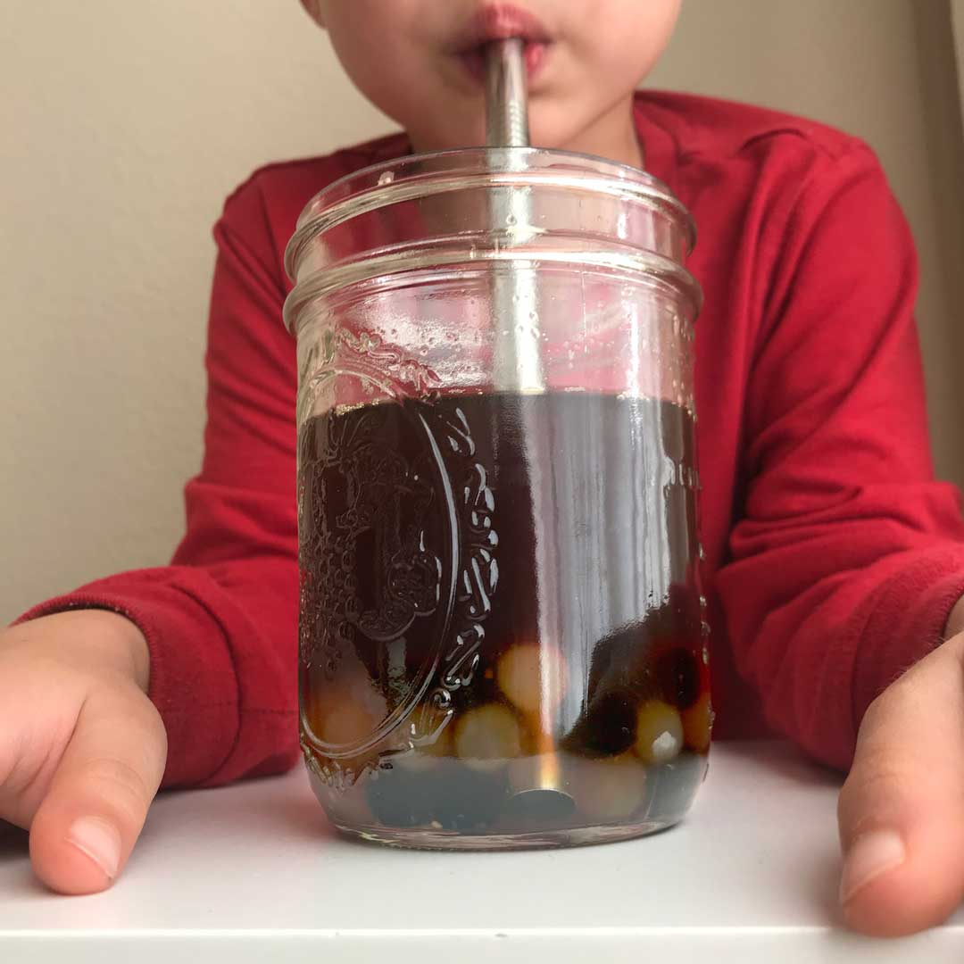 Tea with boba in mason jar with metal boba straw
