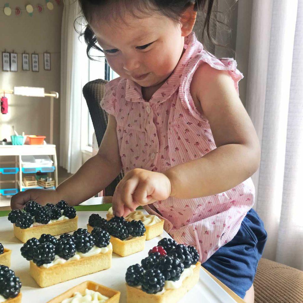 Putting berries onto custard